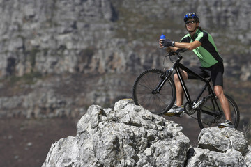 Male mountain biker sitting on bicycle at edge of rock, looking at view, side view