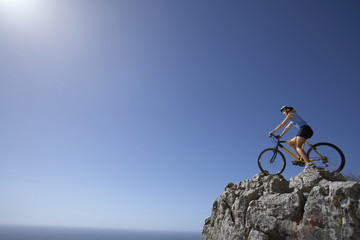 Female mountain biker sitting on bicycle at edge of rock in sunlight, looking at horizon over sea