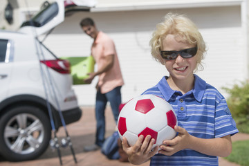 Portrait of smiling boy holding soccer ball in sunny driveway