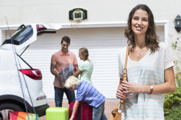 Portrait of smiling woman in driveway with family packing car in background