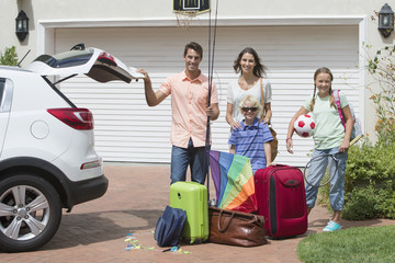 Portrait of smiling family packing car in sunny driveway
