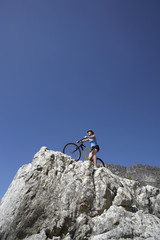 Female mountain biker sitting on bicycle at edge of rock, looking at view, low angle view