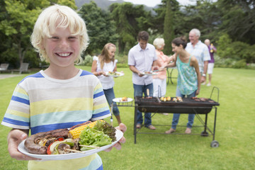 Portrait of smiling boy holding plate of barbecue with family in background
