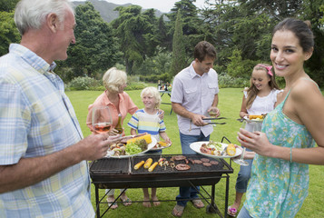 Multi-generation family enjoying barbecue and wine