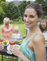 Portrait of smiling woman drinking wine near barbecue