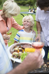 Happy multi-generation family enjoying barbecue and wine