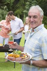 Portrait of smiling senior man holding plate of barbecue and wine