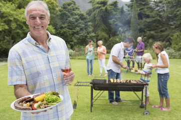 Portrait of smiling senior man holding plate of barbecue and wine with family in background