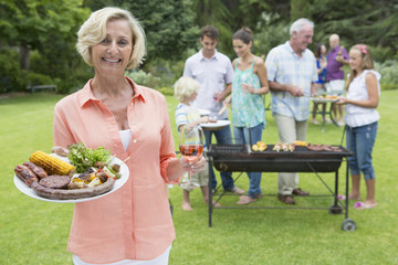 Portrait of smiling senior woman holding plate of barbecue and wine with family in background