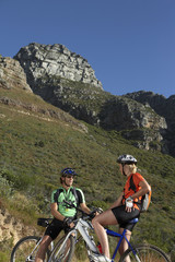 Couple mountain biking in valley, sitting on bicycles, taking break