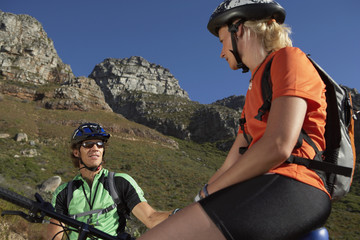 Couple mountain biking in valley, sitting on bicycles, taking break, low angle view