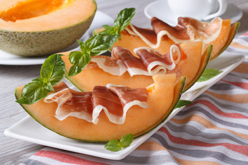 Melon with prosciutto and basil close-up horizontal