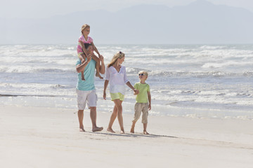 Family walking on sunny beach