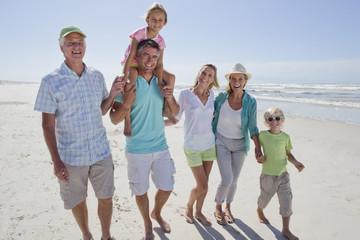 Portrait of smiling multi-generation family walking on sunny beach