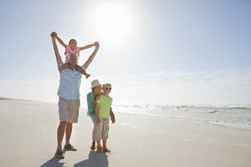 Grandparents and grandchildren walking on sunny beach