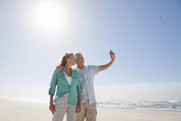 Senior couple with digital camera taking self-portrait on sunny beach
