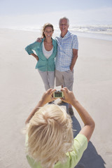 Grandson with digital camera photographing grandparents on sunny beach