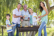 Multi-Generation Family Enjoying Barbeque By Lake