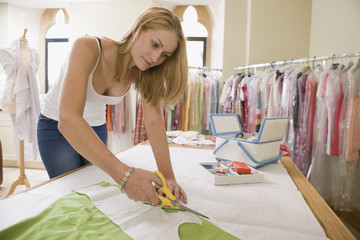 Fashion Designer Cutting Out Pattern From Fabric In Studio