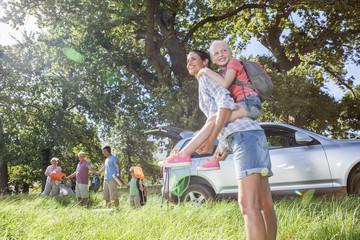 Multi-Generation Family Unpacking Car On Camping Trip