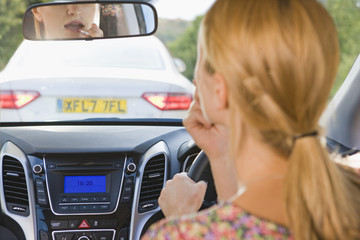 Female Driver Putting On Lipstick Whilst Driving