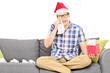 Sad man with Santa hat wiping his eyes from crying