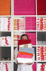 Man shopping in department store, holding large pile of towels, face obscured, shelves in background