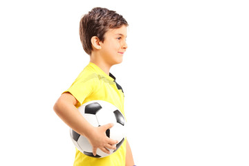 Young boy walking and holding a football isolated on white