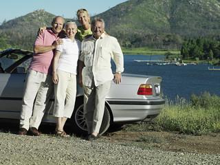 Two senior couples standing beside convertible car near lake, smiling, portrait
