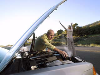 Senior man checking car engine at roadside, woman hailing oncoming traffic on country road