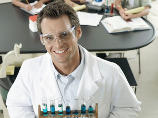 Science teacher standing in classroom, holding rack of test tubes, smiling, portrait, elevated view