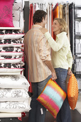 Couple shopping for cushions in department store, woman placing hand on man's shoulder, smiling