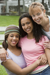 Three young women embracing, smiling, front view, portrait