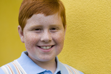 Boy (9-11) with freckles and ginger hair standing beside yellow wall, smiling, close-up, portrait