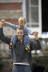 Father carrying son (3-5) on shoulders, smiling, front view, portrait