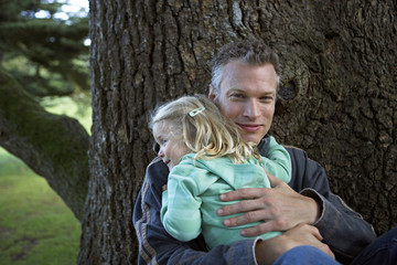 Father embracing daughter (3-5) beside tree in garden, smiling