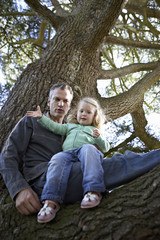 Father and daughter (3-5) sitting in tree, portrait, low angle view
