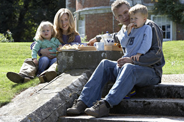 Two generation family sitting on steps in garden, having tea and sandwiches, smiling, portrait