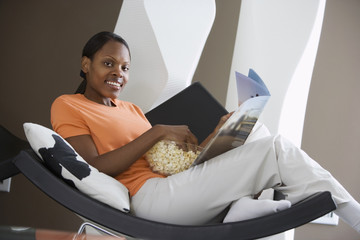 Woman relaxing in curved chair at home, reading magazine, feet up, smiling, side view, portrait (tilt)