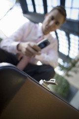 Businessman crouching, using mobile phone, focus on briefcase in foreground (tilt)