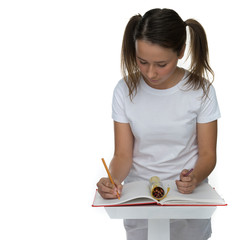 Young schoolgirl writing class notes