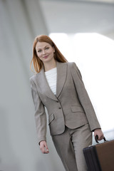Businesswoman carrying briefcase, smiling, portrait (tilt)