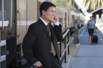 Businessman, with luggage, standing beside stationary train on railway platform, using mobile phone, side view