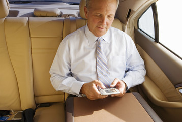 Senior businessman sitting in back-seat of car, using personal electronic organiser, front view