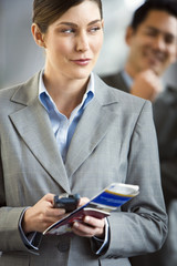 Businesswoman standing in airport terminal, holding mobile phone and ticket, making sideways glance
