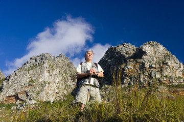 Mature man hiking on mountain trail, leaning on hiking pole, admiring scenery, smiling, low angle view