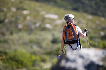 Mature woman hiking on mountain trail, carrying rucksack and using hiking pole, rear view