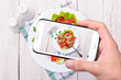 Hands taking photo vegetable salad with smartphone