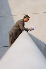Mature businessman leaning on balcony railing, reading document, profile (surface level)