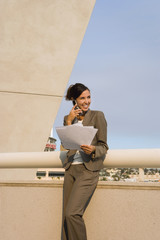 Businesswoman leaning on balcony railing, holding document, smiling